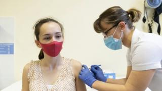 A medical worker administers the Sputnik V vaccine to a young woman in Hungary, 13 April 2021