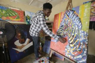 Kreevious Bachue paints an artwork at his Farchure Print ^ Gallery workshop in Monrovia, Liberia. 17 June 2020. Kreevious Bachue is a professional artist, who started to paint at age 6, while in primary school, later, at age 12, he enrolled at the Child Arts Liberia institute to further advance his artistic career. Bachue produces paintings both at his workshop and at home and sells to various art shops and galleries. In the Farchuree Print ^ Gallery workshop, Bachue gives lessons to others about paiting.