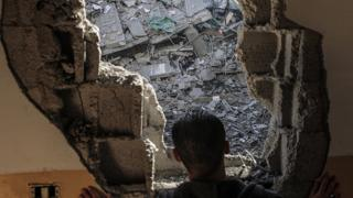فلسطيني ينظر من داخل منزله الذي تعرض للقصف