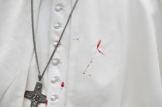The pope's white tunic is stained with blood.