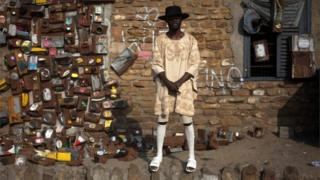 An artist poses by his pieces of art exposed during the Chale Wote street art festival in Accra, on 21 August 2016