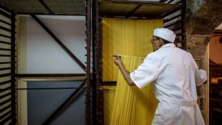 A man dries fresh pasta in a factory
