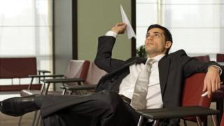 Oficinista jugando con un avión de papel