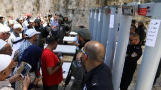 Palestinians stand in front of Israeli policemen and newly installed metal detectors at an entrance to the compound known to Muslims as Noble Sanctuary and to Jews as Temple Mount, in Jerusalem's Old City 16 July, 2017