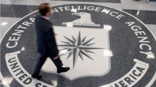 man walking over CIA logo on floor