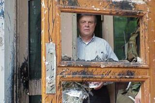 Ambassador James Sasser looks through the broken doors of the a US embassy building in Beijing