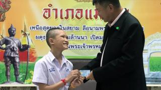 Mongkol Boonpiam (L) as he receives Thai citizen ID card from Mae Sai District Chief Somsak Kanakham (R)