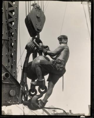 A labourer hangs on a connector in the sky.
