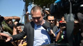 Empresário Joesley Batista cercado de jornalistas e vestindo um terno sem gravata