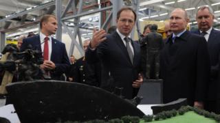 Владимир Путин смотрит на можель памятника.