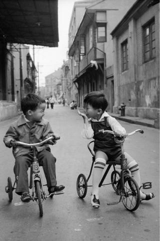 Two boys sit on bikes in the street