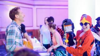 James Roberts amused by a fan's replica head of Trailbreaker at TFNation 2017