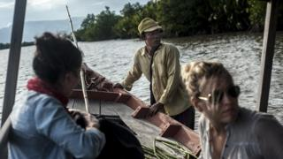 Tourists join Him Sim on a boat trip around the mangroves