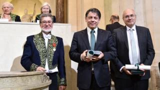 Marcelo Viana é o do meio, à direita dele, também de terno, é o francês com quem ele divide o prêmio, e à esquerda é um membro da Academia de Ciências da França.