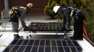 Solar panel installers work on a roof in San Francisco, California