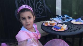 Alaynna in her princess costume eating party food