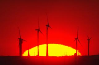 The sun rises behind wind turbines near the Pankow motorway junction, Berlin