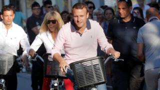 Emmanuel Macron and his wife, Brigitte Trogneux, riding bikes near their home on Saturday