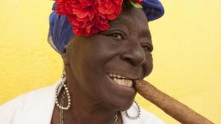 Mulher cubana posa com charuto na boca