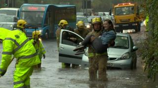 Firefighters helping motorist from vehicle during flood