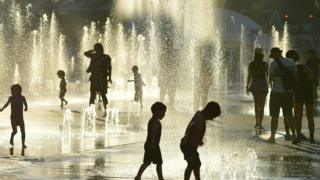 Montreal children cool off at a water fountain in the midst of a deadly heat wave