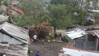 Imagem mostra pessoas próximas a casas danificadas e árvores caídas com a passagem do Ciclone Keneth, em Comores