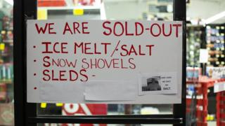 A sign says a shop is sold out of salt, snow shovels and sleds