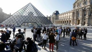 Journalists stand outside the Louvre as it reopens to the public for the first time since March