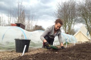 Sinead Fenton digs in the soil with a trowel