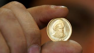 File photo showing an Iranian gold trader holding a gold coin in Tehran (19 April 2006)