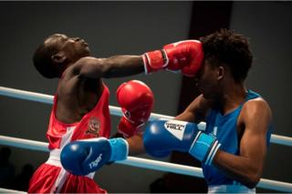 A boxer in red punches his opponent, dressed in blue, on the head.