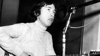 George Young playing the guitar