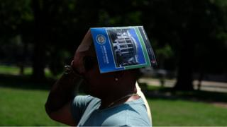 A tourist uses a guide book to cover their head