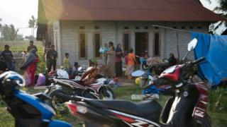 Residents stand outside a house as they are afraid to stay indoors in their homes in Palu in Central Sulawesi on September 29, 2018