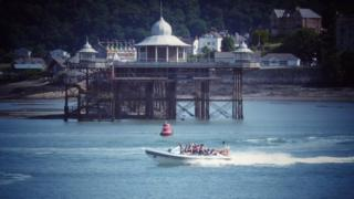 A packed speedboat passes Bangor pier on the Menai Strait, Gwynedd