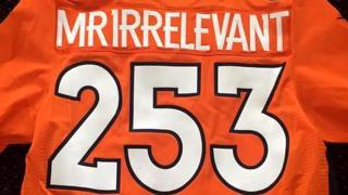 Una camiseta naranja con el número 253