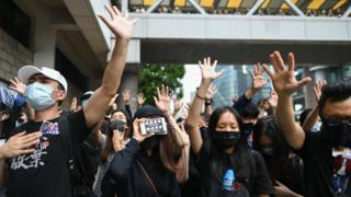 Masked protesters gesture to symbolise their five demands outside the High Court premises.