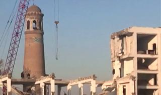 A crane and partially demolished buildings stand next to the minaret