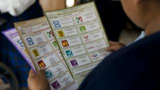 Mujer con cédulas de votación