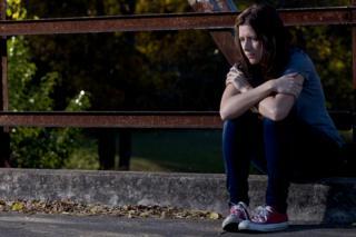 Woman sitting on a curb