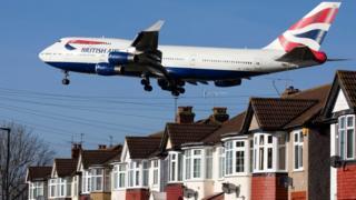 British Airways plane above houses