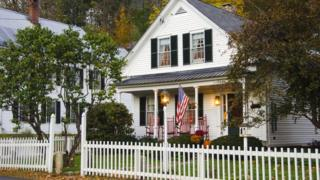 House with white picket fence and American flag
