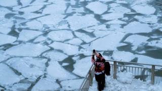Imagem moistra pessoa fotografando lago congelado em Chicago, em meio à onde de frio que atinge os EUA