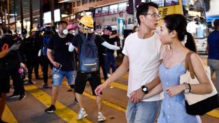 香港尖沙咀一對男女在黑衣示威者中走過(10/8/2019)
