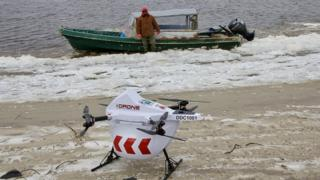 Drone sits on beach if front of a speed boat