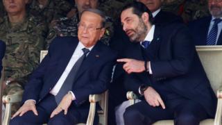 Lebanese President Michel Aoun (L) speaks to caretaker Prime Minister Saad Hariri (R) at a military parade on 22 November 2019