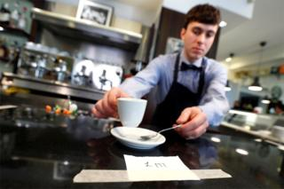 A waiter serves a coffee with a sign saying '1 metre'