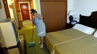 Una mujer limpiando una habitación de hotel en España