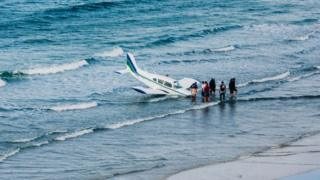 The plane landed in the sea on the edge of the beach