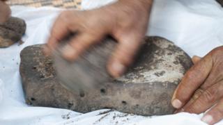 Mão triturando raízes com uma pedra